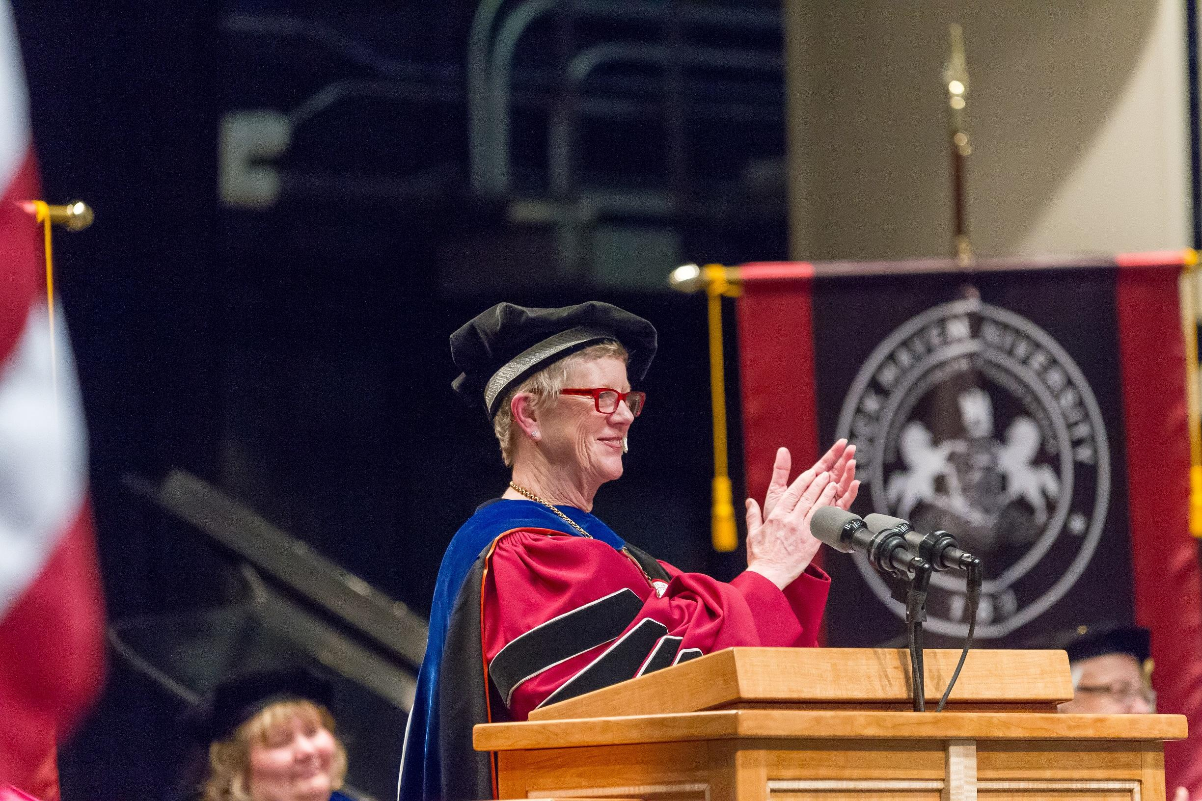 Dr. Donna Wilson, interim president, applauds the new graduates during Lock Haven University's graduate commencement ceremony on Friday, May 11.